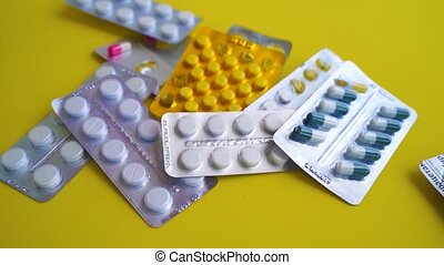 Close up of medical blister packs with tablets on yellow background. Packs with various tablets. Concept of threat of various diseases