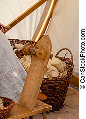 Close-up of medieval woman processing wool on yarn. Medieval spinning wheel. Vertical photo.