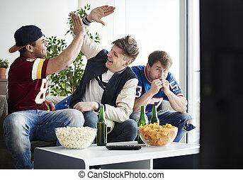 Close up of men cheering their sport team success