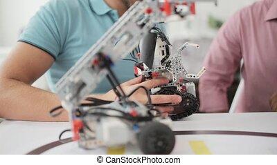 Close up of men discussing robot