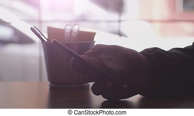 Close up of men hands use mobile phone and drinks coffee by the window in cafe. 3840x2160