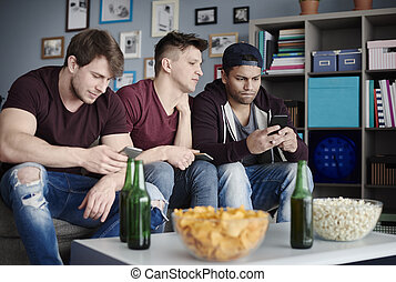 Close up of men with smartphones in the living room