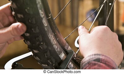 Close-up of men's hands with a specialized wrench on a stand in the workshop tightening the spokes of the wheel eliminating the beating of the rim