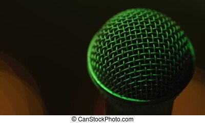 Close-up shot of a microphone with green light and yellow light background