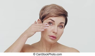 Close-up of middle aged mature woman over white bacjground. ...