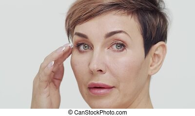 Close-up of middle aged mature woman over white bacjground. Portrait of mature lady. Plastic surgery, beauty injections, cosmetology concept.
