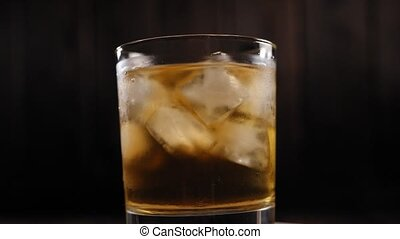 Close-up of misted glass of whiskey with ice slowly rotates on a dark background