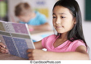Close up of mixed race girl reading book