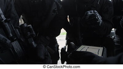 Close-up of mixed-race military soldiers with rifles planing and discussing their plan at base 4k