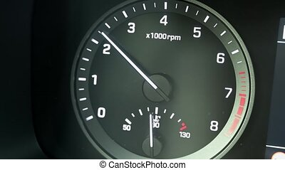 Close up of modern automotive tachometer on black background. The tachometer needle rises.