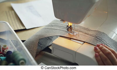 Close-up of modern electric sewing machine working stitching...