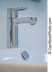 Close-up of modern water tap sink with faucet in minimalistic style in expensive loft bathroom, soft focus, copyspace