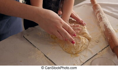 Close-up of mother and little daughter kneading dough together in the kitchen.