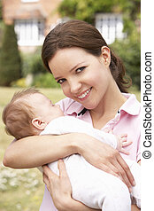 Close Up Of Mother Cuddling Newborn Baby Boy Outdoors At Home