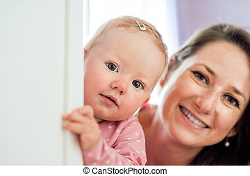 Close up of mother holding her cute baby daughter
