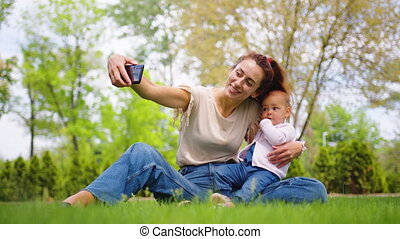 Close up of mother with baby daughter posing for cell phone selfies outdoor.