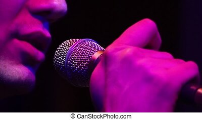 Close up of mouth of the male singer performs song in microphone on concert