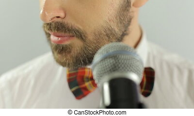 Close up of mouth of the singer performs a song in a microphone on a white background