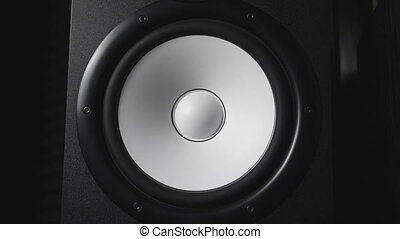 Close up of moving modern sub-woofer on recording studio. White round audio speaker pulsating and vibrating from sound on low frequency. Work of high fidelity loudspeaker membrane. Slow motion.