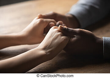 Close up of multiracial couple holding hands in cafe