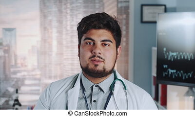 Close-up of multiracial doctor in lab coat and with...