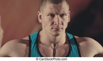 Close up of muscular bodybuilder stands in front of the mirror in the gym