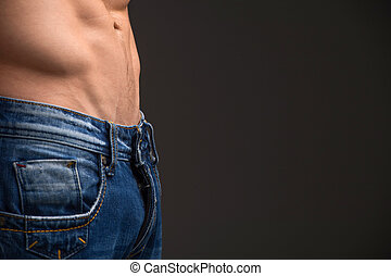 Close up of muscular male abdomen and blue jeans. Standing isolated over dark background and copy space to the right side