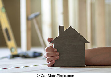 Close-up of muscular male hand holding small model house on blurred background of building tools in room under construction. Investments in real estate property and ownership of dream home concept.