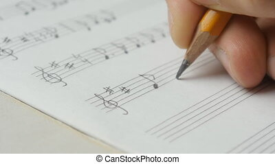 Close up of music writing. Musician composing with a pencil:...