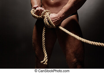 Close-up of naked muscled man tied with rope