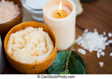 close up of natural body scrub and candle on wood