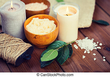 close up of natural body scrub and candles on wood