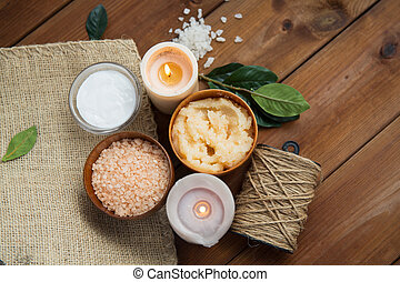 beauty, spa, therapy, natural cosmetics and wellness concept - close up of body scrub with himalayan pink salt and candles on wood