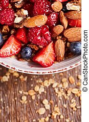 Close up of natural fresh ingredients for healthy breakfast strawberry, blueberry, almonds, granola in a white bowl on a wooden background.
