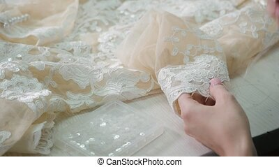 close-up of needle and thread, embroider pattern. Equipment for sewing elegant wedding dress. Hand made