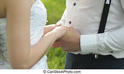 Close up of newlyweds fingers gently touch each other. Happy caucasian couple holding hands.