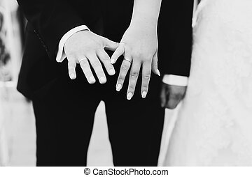 Close-up of newlyweds hands with wedding rings