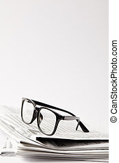 close up of newspapers with black eyeglasses, on white with copy space