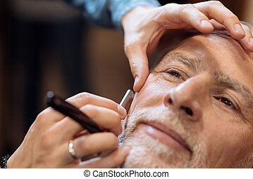 Close up of nice senior man being shaved at barbershop