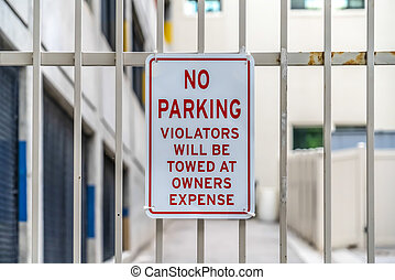 Close up of No Parking sign on awhite metal gate with building in the background