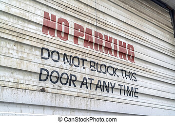 Close up of No Parking sign painted on the corrugated metal door of a building