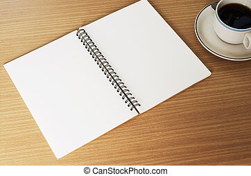 Close up of Notebook and coffee cup on wood table backgrounds