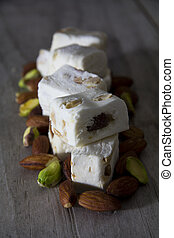 Close Up of Nougat on a Table with Almonds and Pistachios - Selective Focus