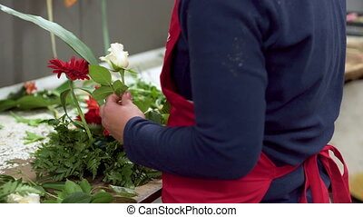 Close up of of woman florist creating bouquet of flowers . -...