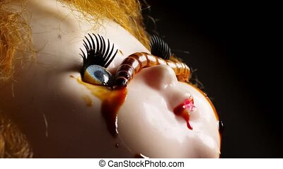 Close up of old dirty creepy doll with mealworms.