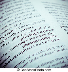 Close up of old English dictionary page with word Photographer. Shallow depth of field and toned page of word Photographer on English dictionary .