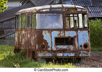 Close-up of old forsaken passenger bus with broken windows rusting in high green weedy grass on edge of plowed brown field on bright spring day under blue morning sky.