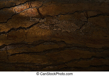 Close-up of old stony cracked wall in darkness
