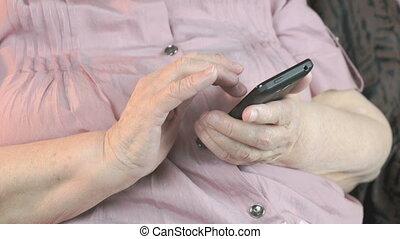 Close up of old wrinkled hands holding smartphone