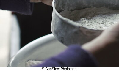 Close up of old wrinkled woman's hands sifting flour